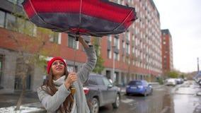 Mujer femenina joven, muchacha con el paraguas que se coloca al aire libre La ráfaga del viento saca del paraguas la mano Muchach almacen de metraje de vídeo