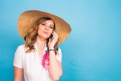 Mujer femenina sonriente que habla en el teléfono en un fondo azul Fotos de archivo libres de regalías