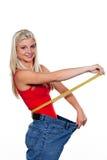 Mujer fina con cinta métrica y los pantalones vaqueros grandes Imagen de archivo libre de regalías