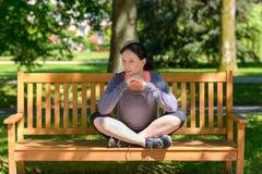 Mujer flexible atractiva que se sienta en un banco de parque fotografía de archivo libre de regalías