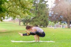 Mujer flexible fuerte que se resuelve en un parque fotos de archivo libres de regalías