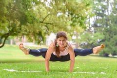 Mujer flexible fuerte que se resuelve en un parque imagen de archivo