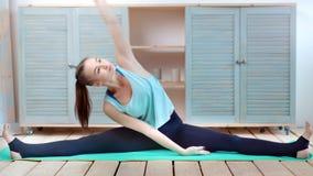 Mujer flexible joven que hace estirar la sentada en tiro lleno interior de la guita en casa almacen de metraje de vídeo