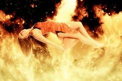 Mujer flotante hermosa en el fuego Imagen de archivo libre de regalías