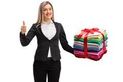 Mujer formalmente vestida con una pila de ropa envuelta con rojo fotos de archivo libres de regalías
