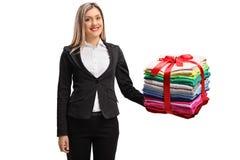 Mujer formalmente vestida que sostiene una pila de coágulo planchado y lleno foto de archivo libre de regalías