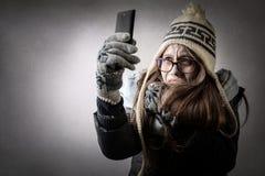 Mujer fría que mira smartphone Imágenes de archivo libres de regalías
