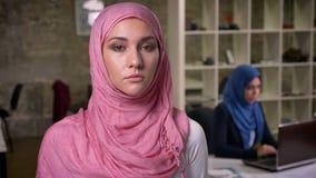Mujer fresca concentrada de Oriente Medio del og de la mirada con las caras serias y posición derecha confiada en la oficina del  metrajes