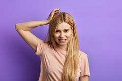 Mujer frustarted enojada joven que rasgu?a la cabeza con la mano imágenes de archivo libres de regalías