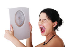 Mujer frustrada con la escala Imagenes de archivo