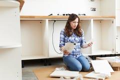 Mujer frustrada con muebles de la asamblea del uno mismo en cocina imagen de archivo