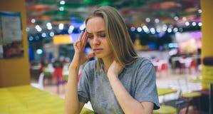 Mujer frustrada con un dolor de cabeza en zona de restaurantes un fondo unfocused Foto de archivo libre de regalías