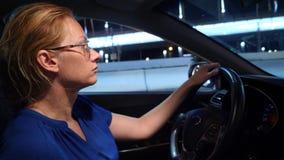 Mujer frustrada pegada en un atasco Mujer de negocios en la noche en un atasco detrás de la rueda de un coche, contra a metrajes