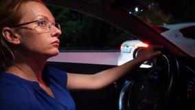 Mujer frustrada pegada en un atasco Mujer de negocios en la noche en un atasco detrás de la rueda de un coche, contra a almacen de video