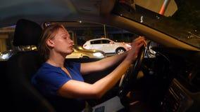 Mujer frustrada pegada en un atasco Mujer de negocios en la noche en un atasco detrás de la rueda de un coche, contra a almacen de metraje de vídeo