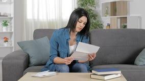 Mujer frustrada que lee una letra en casa almacen de metraje de vídeo