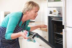 Mujer frustrada que mira en Oven With Disappointed Expression Fotos de archivo libres de regalías