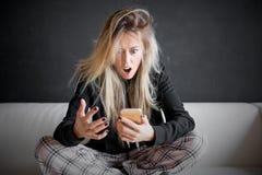 Mujer frustrada que mira su teléfono Foto de archivo