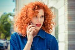 Mujer frustrada, roja enojada del pelo rizado que habla en la situación del teléfono móvil afuera fotos de archivo