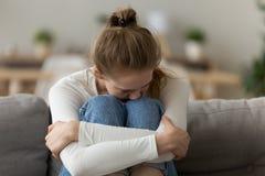 Mujer frustrada trastornada que se sienta en el sofá, rodillas del abrazo, teniendo problema imágenes de archivo libres de regalías