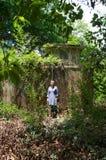 Mujer fuera del edificio abandonado overgrown Fotos de archivo