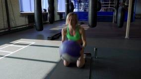 Mujer fuerte joven con el cuerpo perfecto de la aptitud en ropa de deportes que ejercita con la bola de medicina en el gimnasio M almacen de video
