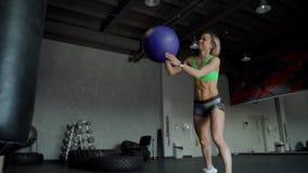 Mujer fuerte joven con el cuerpo perfecto de la aptitud en ropa de deportes que ejercita con la bola de medicina en el gimnasio M metrajes