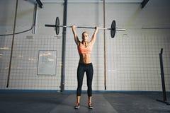 Mujer fuerte joven que hace el levantamiento de pesas Imagen de archivo libre de regalías