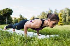mujer fuerte joven que hace pectorales en prado de la hierba imagenes de archivo
