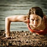 Mujer fuerte que hace el pushup Foto de archivo libre de regalías
