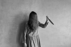 Mujer furiosa con el pelo largo y un cuchillo Fotografía de archivo libre de regalías