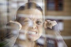 Mujer furiosa en ventana Fotografía de archivo libre de regalías