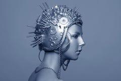 Mujer futurista en casco del metal con los tornillos, las nueces y las cadenas fotos de archivo libres de regalías