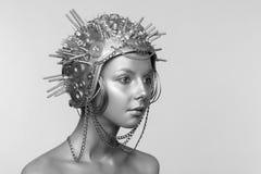 Mujer futurista en casco del metal con los tornillos, las nueces y las cadenas imágenes de archivo libres de regalías