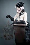 Mujer gótica con un birdcage vacío Imágenes de archivo libres de regalías