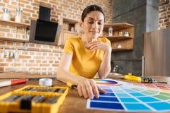 Mujer gay feliz que selecciona el color para la pared Fotografía de archivo