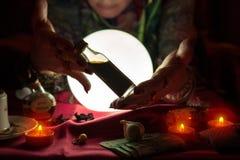 Mujer gitana del adivino que muestra la botella con la poción Imagen de archivo libre de regalías