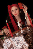 Mujer gitana que se sienta con las tarjetas. Aislado imagen de archivo libre de regalías