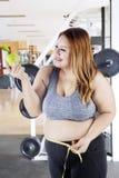 Mujer gorda con la manzana y la cinta de la medida Imagen de archivo libre de regalías