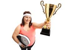 Mujer gorda con una escala del peso y un trofeo de oro imagenes de archivo