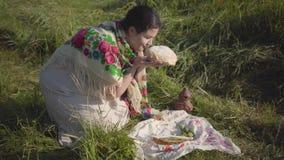 Mujer gorda de Beautifu que se sienta en hierba salvaje con la barra de pan y el tarro de tierra que se preparan para comer tradi almacen de metraje de vídeo