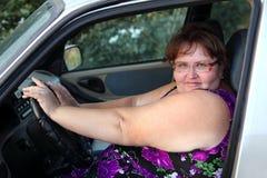 Mujer gorda detrás de la rueda Imagen de archivo libre de regalías