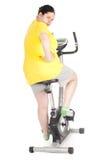 Mujer gorda en la bicicleta inmóvil de la aptitud Foto de archivo libre de regalías