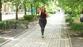 Mujer gorda en vaqueros en el parque con un teléfono metrajes