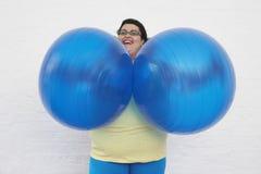 Mujer gorda feliz que sostiene bolas del ejercicio foto de archivo