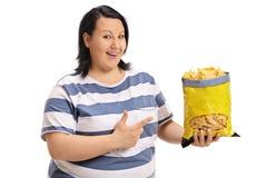 Mujer gorda feliz que sostiene un bolso de microprocesadores y de señalar Imagen de archivo