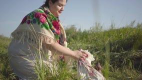 Mujer gorda hermosa que se sienta en hierba salvaje con el tarro de tierra y que separa un pañuelo con la preparación de la comid almacen de metraje de vídeo