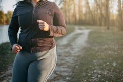 Mujer gorda joven que corre en luz de la salida del sol Foto de archivo