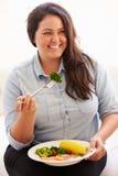 Mujer gorda que come la comida sana que se sienta en el sofá Foto de archivo libre de regalías