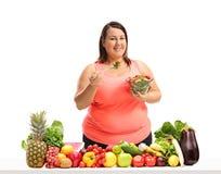 Mujer gorda que come una ensalada detrás de una tabla con la fruta y VE Fotografía de archivo